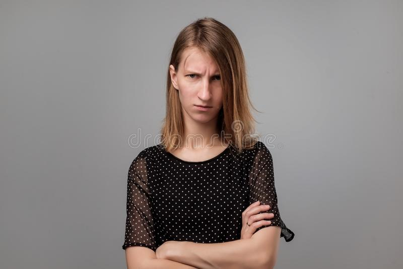 Indoor shot of caucasian woman in black clothes being dissatisfied with something, feels tired and exhausted stock photography
