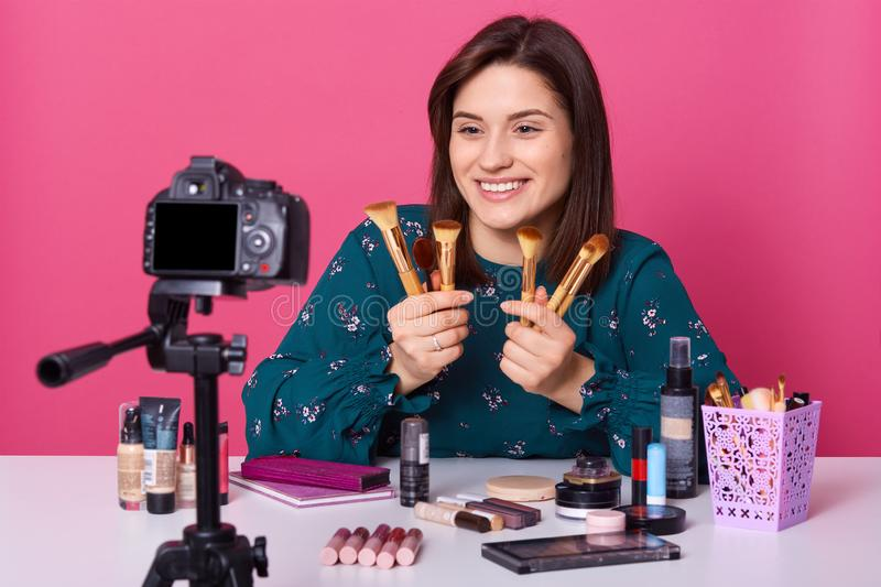 Indoor shot of caucasian woman showing cosmetic powder brush isolated over pink background, recording video blog, brunette female stock photos