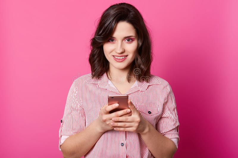 Indoor shot of charming darkhaired female dressed stylish shirt, holding smartphone in both hands and looking at camera, stands. Smiling isolated over pink stock image