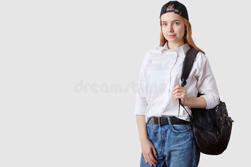 Indoor shot of charming student girl, posing against white studio wall,dressed whit shirt, jeans, visor cap back, looking directly royalty free stock photos