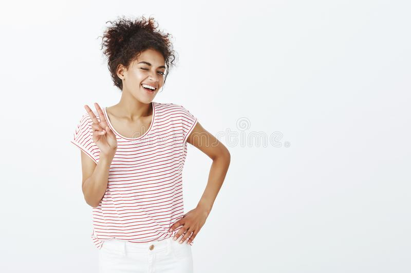 Indoor shot of confident happy and outgoing woman with tanned skin, holding hand on hip, showing victory or peace. Gesture and winking with broad smile at royalty free stock photography