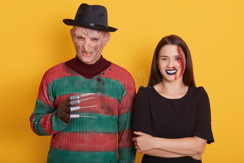 Indoor shot of couple ready to go to halloween party, guy wearing old sweater and black hat, female in black dress, having bloody stock images