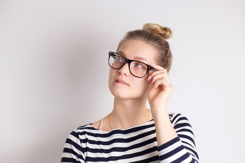 Indoor shot of cute girl looking away, having doubtful and indecisive face expression, pursuing her lips. Confused young female stock image