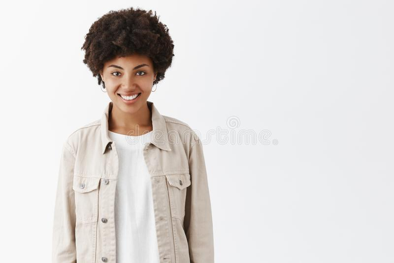 Indoor shot of cute tomboy girl with dark skin and afro hairstyle in trendy beige jacket over t-shirt, smiling broadly royalty free stock photo