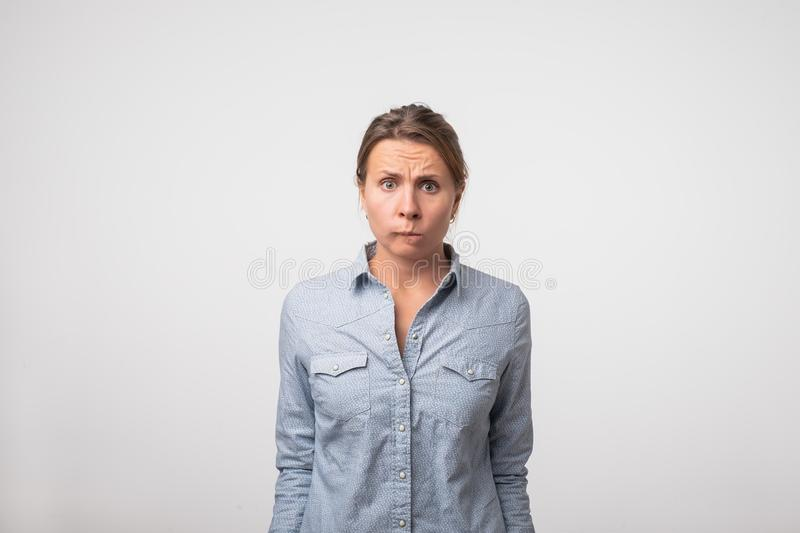 Indoor shot of cute woman in denim shirt in denim shirt having doubtful and indecisive face expression royalty free stock images