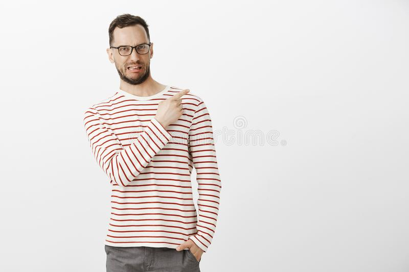 Indoor shot of disgusted displeased funny male model with bristle in black eyewear, sticking out tongue and making stock images