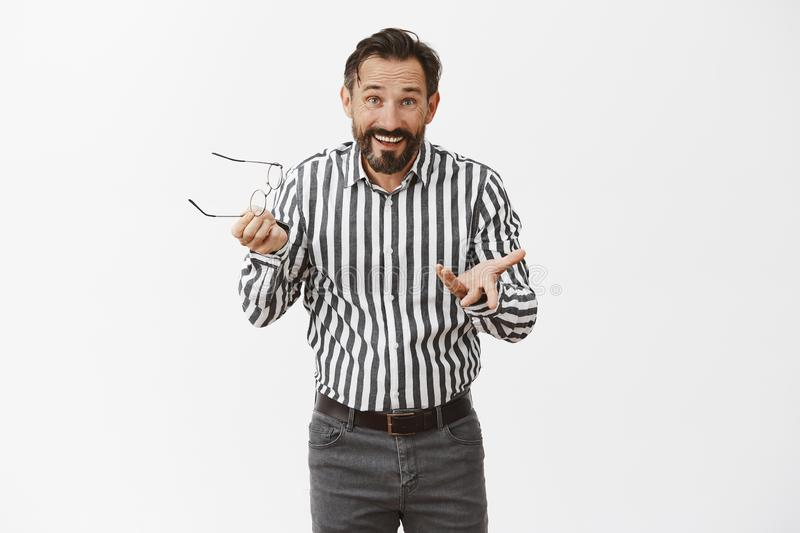 Indoor shot of excited and over-emotive attractive adult male model with short haircut, taking off glasses and gesturing royalty free stock photography