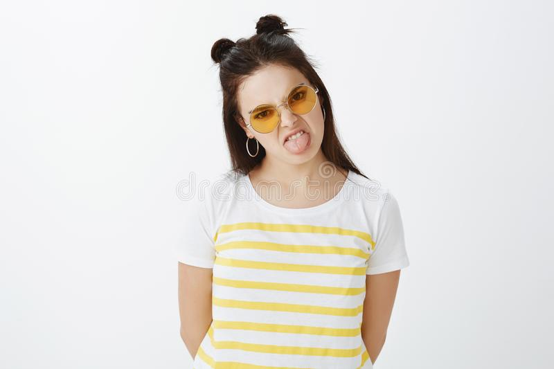Indoor shot of fashionable picky and moody girlfriend in stylish outfit and glasses with hair buns, sticking out tongue. And wrinkling nose, expressing dislike royalty free stock photos