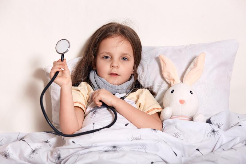 Indoor shot of female child waits for pediatrician doctor for examining little girls heart lungs to check for problems, charming. Sick kid lying in bed with her royalty free stock photo