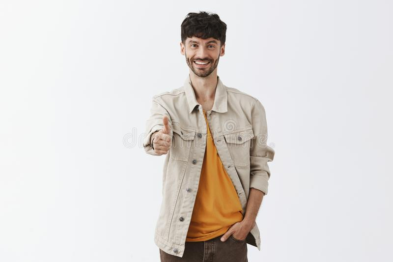 Indoor shot of friendly upbeat and satisfied handsome mature male entrepreneur in trendy outdoor clothes pulling hand. Towards camera in thumb up gesture stock image