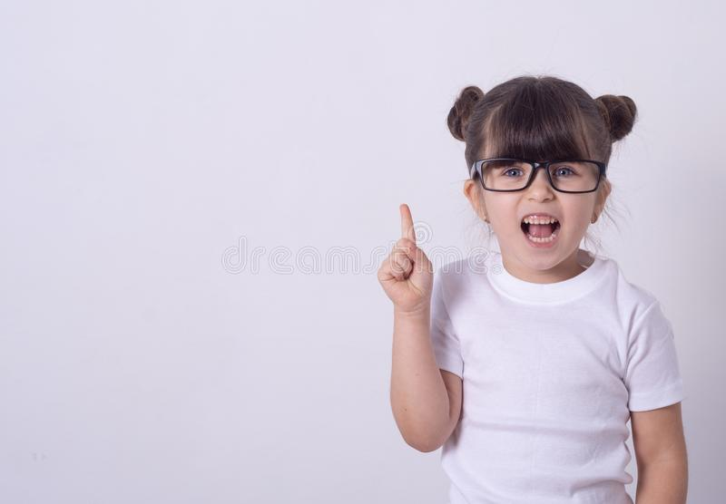 Indoor shot of friendly young girl laughing and smiling joyfully raising hands royalty free stock photography