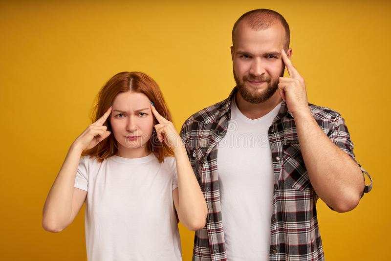 Indoor shot of frustrated thoughtful adult woman and man keep fingers on temples, try to concentrate on difficut question, stand stock images
