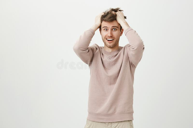 Indoor shot of funny handsome guy messing his hair while rubbing head, expressing devastation and acting crazy, standing. Over gray background. Guy is shocked stock images
