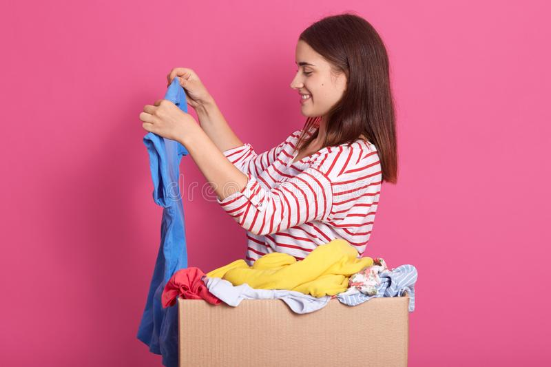 Indoor shot of girl stands with blue shirt near cardboard box full of fashionable clothes, lady wearing striped shirt, isolated royalty free stock images