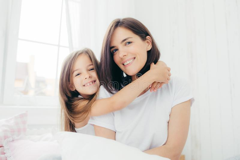 Indoor shot of good looking brunette mother with gentle smile and her small daughter gives hug, enjoy domestic atmosphere, pose ag stock images