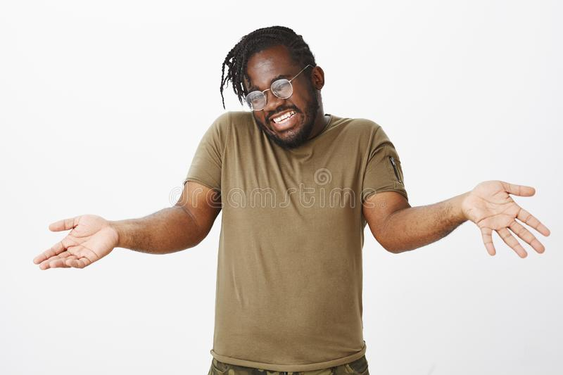 Indoor shot of good-looking careless african-american with beard and trendy haircut, raising palms and shrugging with. Clueless gesture, being unaware and royalty free stock photography