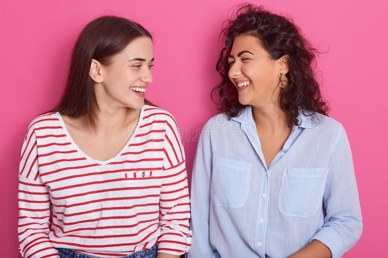 Indoor shot of good looking women with positive expressions, looking at each other, wearing casual clothes, models posing against stock images