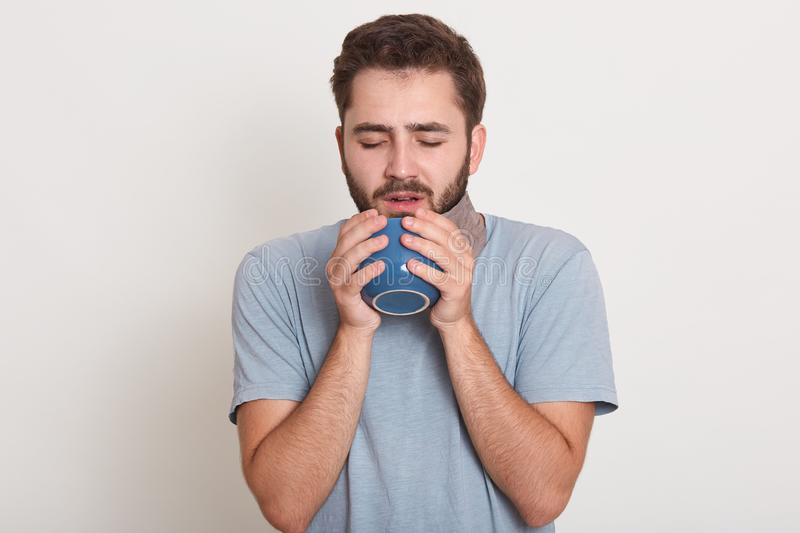 Indoor shot of handsome bearded man with dark hair and mustache, dressesd in t shirt holding blue cup or mug with good morning tea stock photography