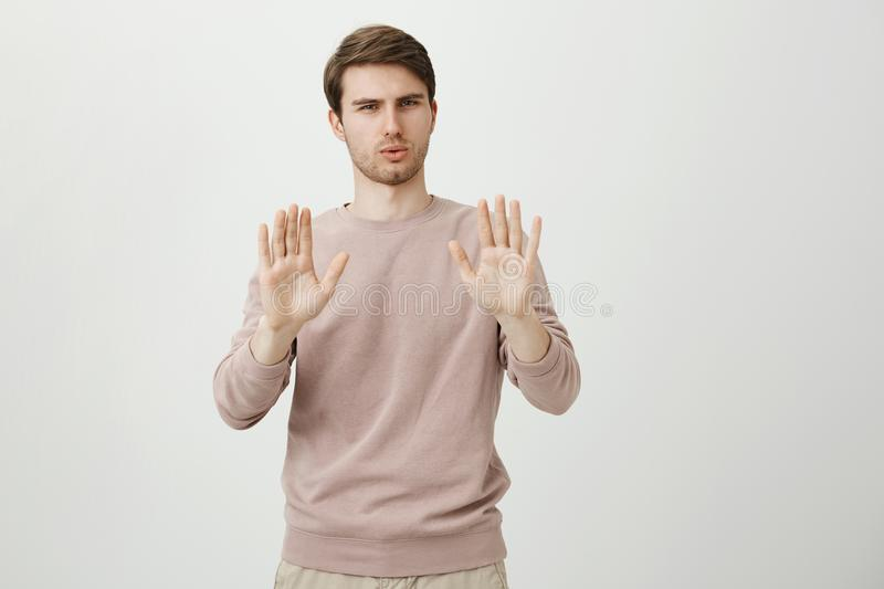 Indoor shot of handsome european male model expressing confidence and showing stop or hold on gesture while being calm stock photo