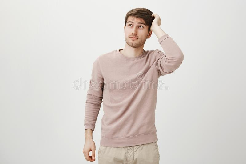 Indoor shot of handsome student with bristle scratching head and looking up, being puzzled or confused, standing over. Gray background. Guy near blackboard do stock image