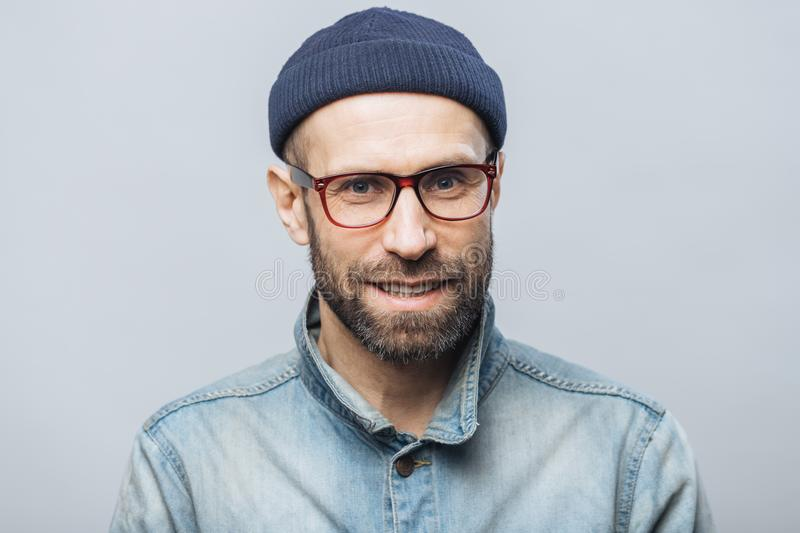 Indoor shot of handsome unshaven male with satisfied expression, rejoices achieving success at work, looks happily through spectac royalty free stock photo