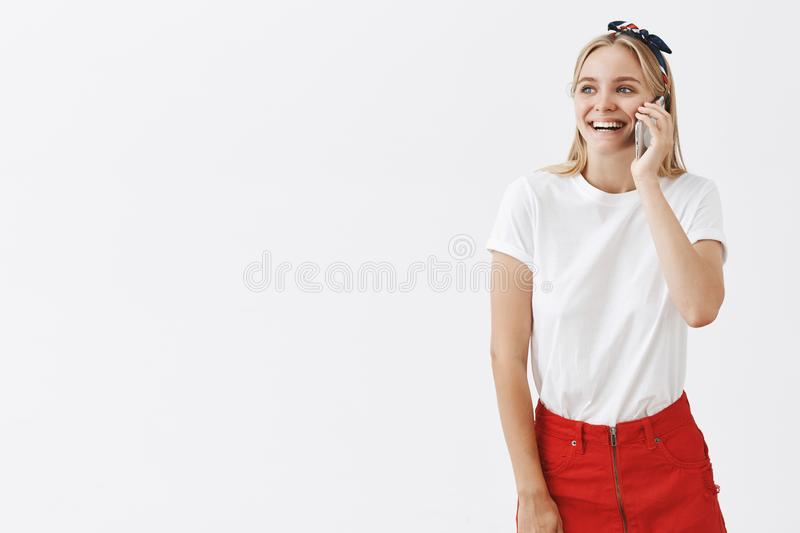 Indoor shot of happy attractive and carefree female blonde in headband and red skirt talking on smartphone and gazing royalty free stock image