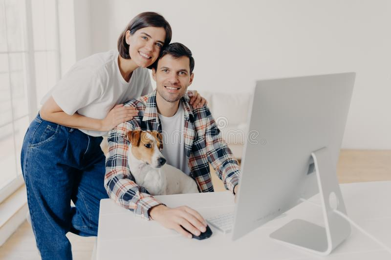 Indoor shot of happy family couple pose near computer monitor, work together remotely, have own business, earn money online, look royalty free stock images