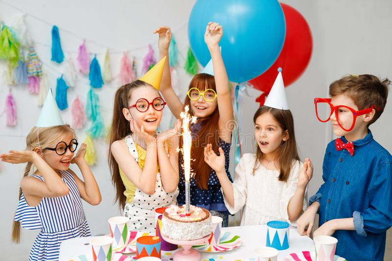 Indoor shot of happy joyful children look at big sparkle on cake, celebrate birthday, wear awkward big spectacles, party royalty free stock photos