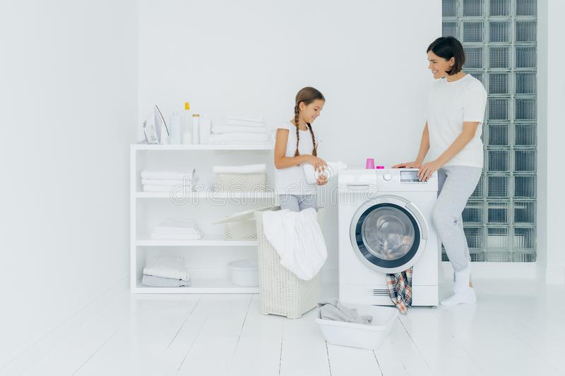 Indoor shot of happy mother and daughter stand near washing machine, girl pours liquid powder, load washer with dirty clothes, do royalty free stock image
