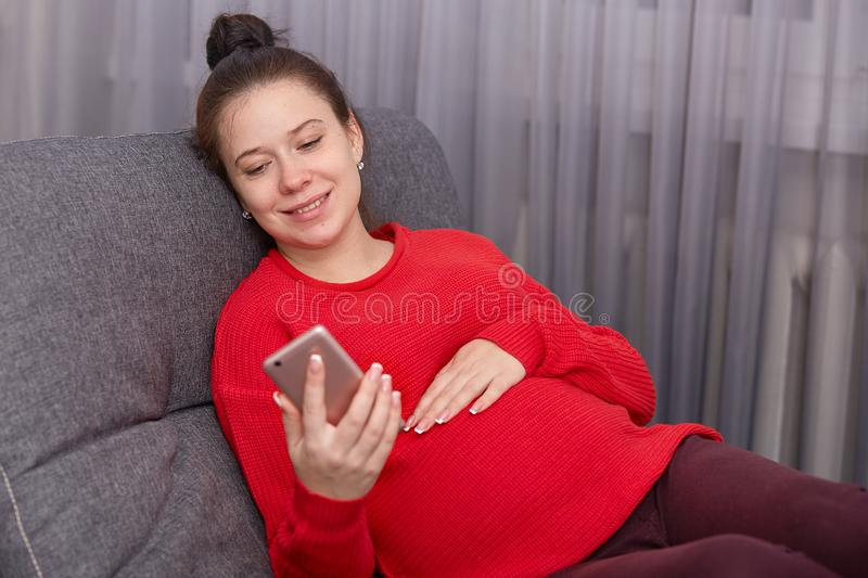 Indoor shot of happy pregnant female holding smart phone, wearing red sweater and leggins, has bunch on head, rests at couch, has. Video call with her husband royalty free stock photos