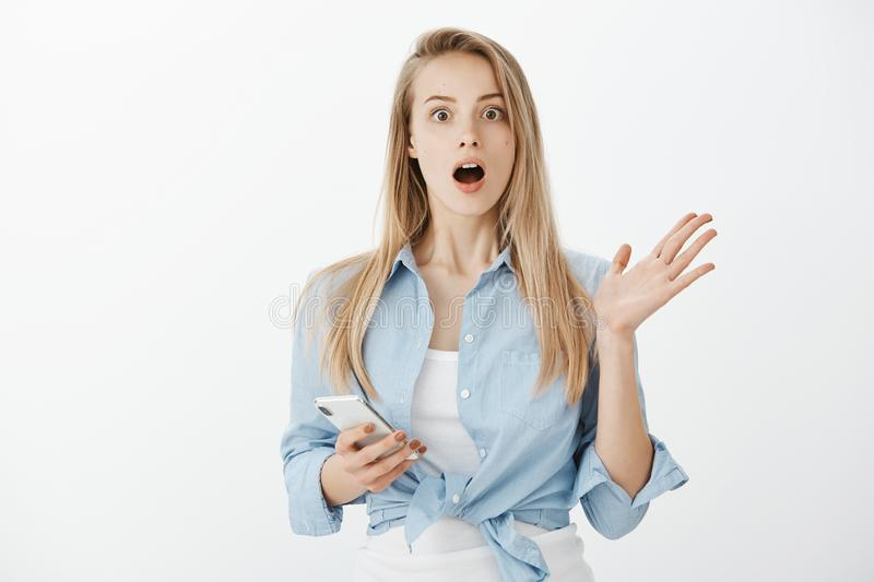 Indoor shot of impressed amazed attractive fair-haired woman in stylish outfit, raising palm and dropping jaw while. Explaining recent news to friend, holding royalty free stock photography