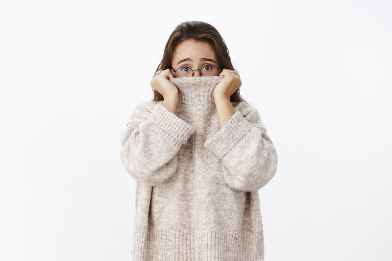 Indoor shot of insecure worried young cute woman in glasses with brown hair pulling collar of sweater on nose and. Frowning nervously as looking scared at stock image