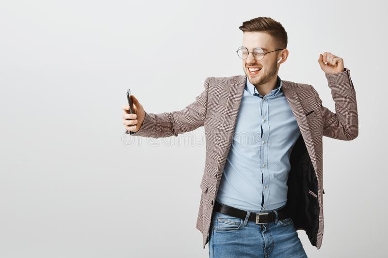 Indoor shot of joyful happy handsome european male entrepreneur in trendy jacket over blue shirt dancing carefree. Holding smartphone singing along song while royalty free stock photos