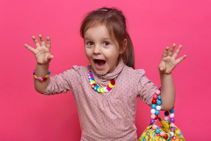 Indoor shot of little funny girl trying to frighten her friends or parents, keeping hands up, screaming like monster, wearing. Shirt with many multicolored royalty free stock photography