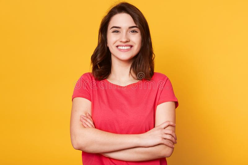 Indoor shot of magnetic beautiful young girl standing with folded arms, looking directly at camera, having sincere smile on her. Face, posing straight  over stock photos