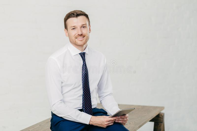 Indoor shot of male financier with positive expression wears formal white shirt with tie, holds modern tablet computer in hands, i. Solated over white background royalty free stock image