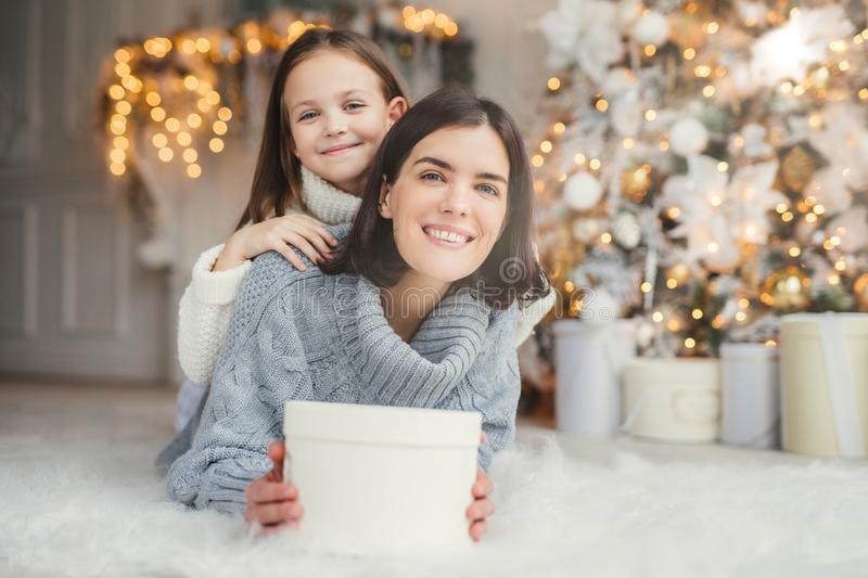 Indoor shot of mother and daughter have fun together, share presents, being in room decorated with garlands and Christmas tree, ha stock photos