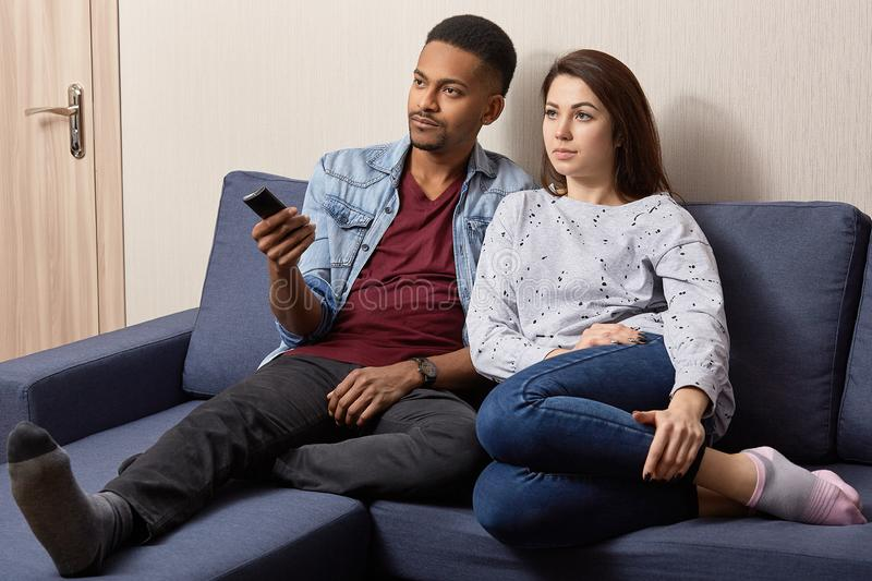 Indoor shot of multiethnic couple watch television at home on comfortable sofa. Black man holds remote control, switches on TV, stock image
