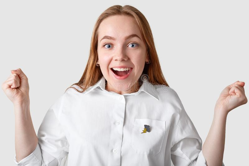 Indoor shot of overjoyed blue eyed young woman with long hair, smiles broadly, being in good mood, rejoices good news, keeps fists royalty free stock photo