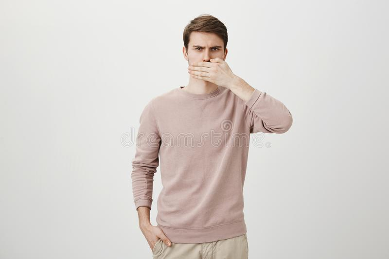 Indoor shot of perplexed and serious european guy covering mouth with hand while holding another in pocket and frowning. At camera over gray background. Man royalty free stock photos