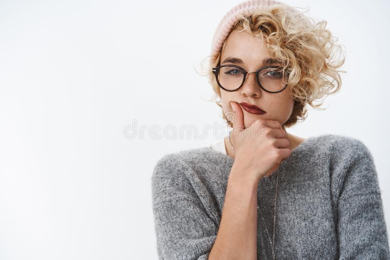 Indoor shot of picky and thoughtful creative female designer making up new ideas wearing warm beanie and winter sweater. With glasses squinting as thinking stock image