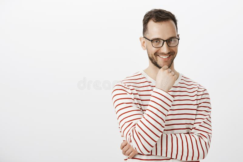 Indoor shot of playful good-looking gay guy in black glasses, smiling with intrigued expression, having some interesting stock photography