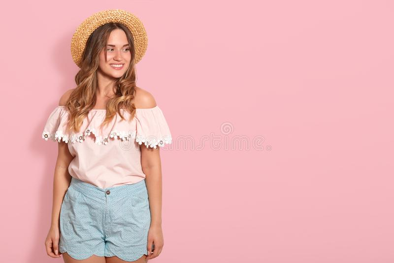 Indoor shot of pleasant looking smiling young woman stands wearing summer hat and fashionable blouse, looks dreamily aside with stock images