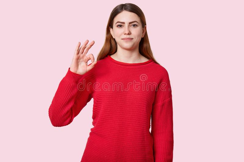 Indoor shot of pleasant looking woman with long dark hair, makes okay gesture, dressed in red jumper, looks directly at camera, stock images