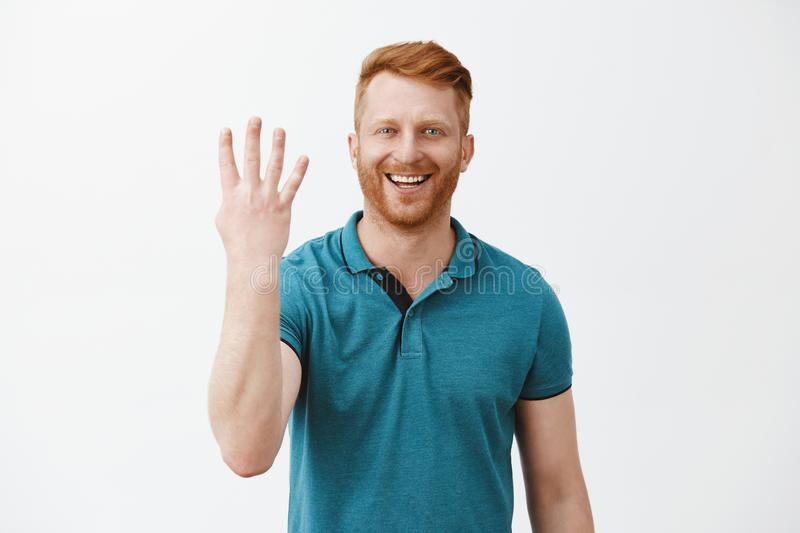 Indoor shot of pleased and satisfied male redhead client with bristle in green polo shirt showing number four with royalty free stock images