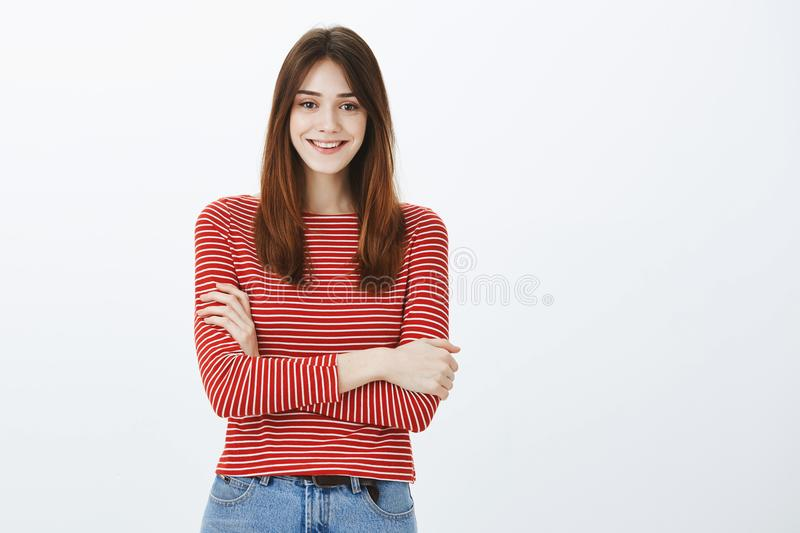 Indoor shot of positive charming european woman with brown hair, holding hands crossed over chest and smiling broadly stock image