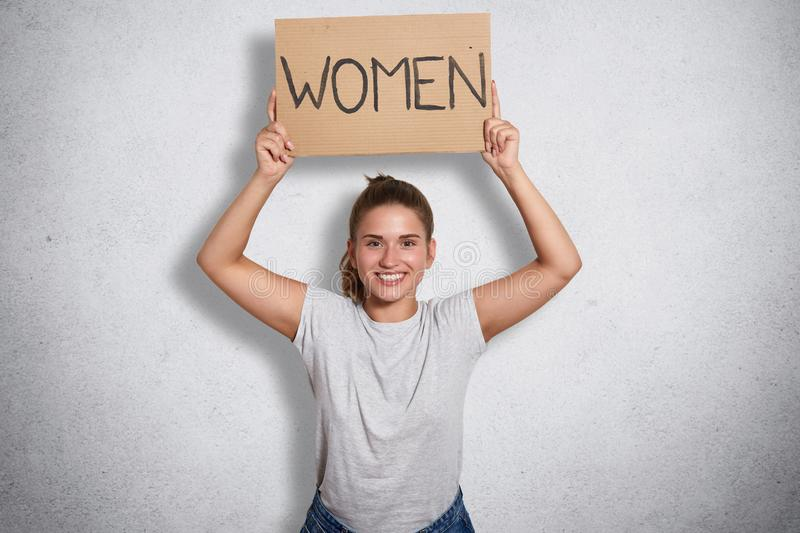 Indoor shot of positive energetic feminist holding sign with inscription women above her head, raising her arms, supporting stock photo