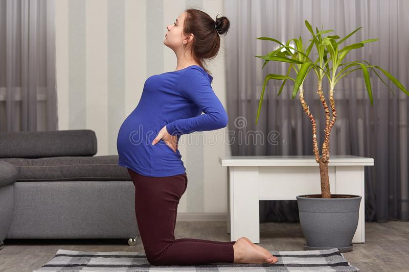 Indoor shot of pregnant lady with hair bun, has big belly, keeps hands on back, dressed in casual clothing, stands on knees, stock images