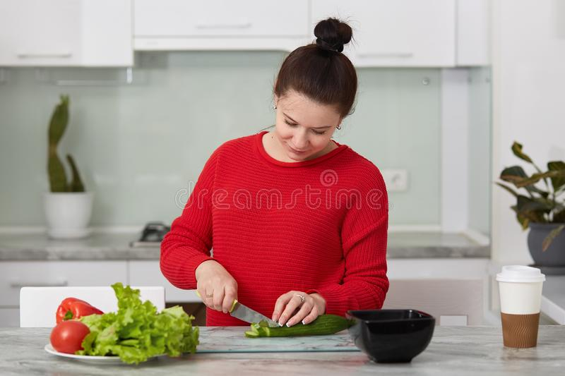 Indoor shot of pregnant woman cooking at home, doing fresh green salad for dinner, eating many different vegetables during stock photos