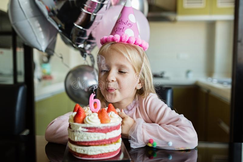 Indoor shot of pretty joyful little girl with blonde hair blowing out the candle, celebrate 6 years old birthday, wear stock photos